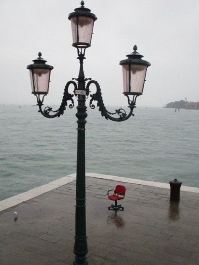 Roter Stuhl am Ufer im Regen