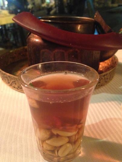 Schwarztee mit frischer Minze und viel Zucker auf gesalzenen Erdnüssen